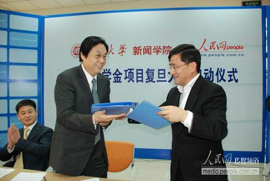 人民网何加正(图左)与复旦大学新闻学院党委书记俞振伟交换合作协议