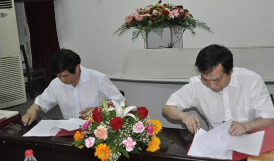 人民网副总裁官建文(左)与华中科技发展基金会秘书长李处长签署奖学金协议