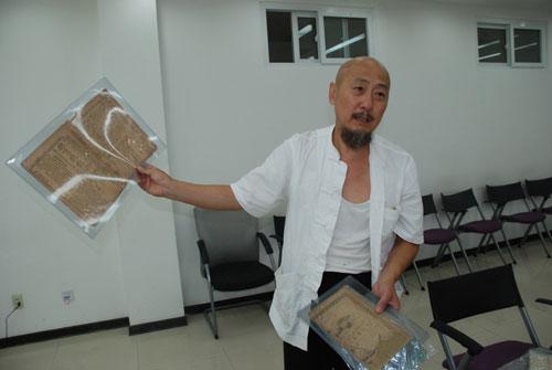 冯艺向记者展示自己的藏品(图片来源:人民网传媒频道 燕帅/摄)