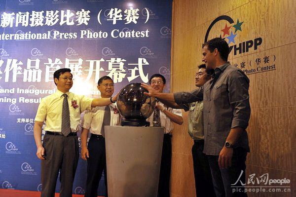 中国新闻摄影学会主席、华赛组委会主席于宁(中)与获奖者一同为华赛作品展开幕启动。 徐星瀚摄